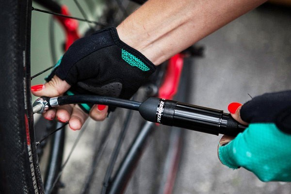A mini hand pump inflating a bike tyre