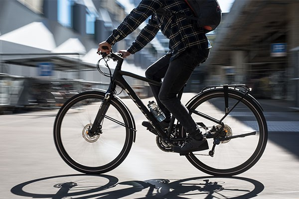 Urban cyclist riding a black hybrid bike in the city