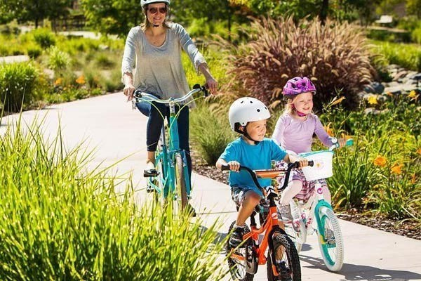 Kids riding a 14 inch and 18 inch kids bike with their family
