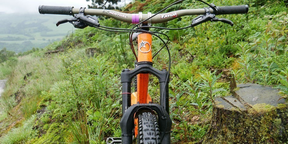 Front view of the Orange bike showing the front suspension forks, handlebars and the Orange logo on the front of the frame