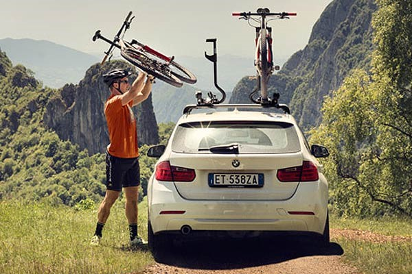 Cyclist mounting a bike to a car roof rack
