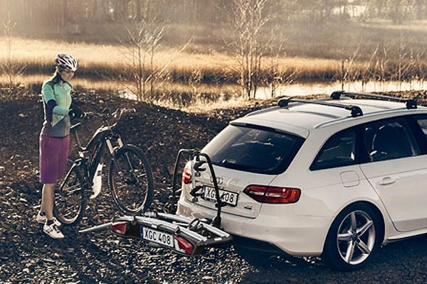 Cyclist rolling a bike onto a towbar car rack