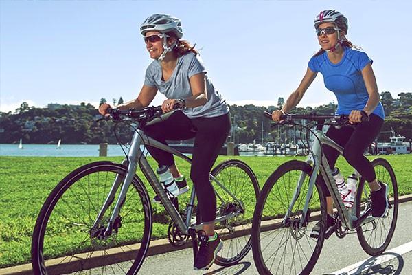 two women riding hybrid bikes