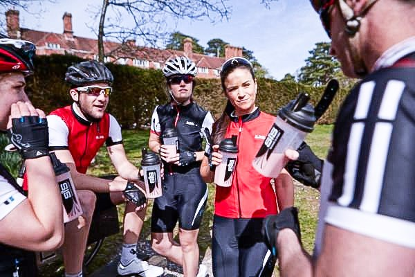 A group of road cyclists taking a break and hydrating themselves.