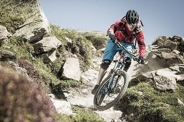 Mountain biker riding through dry, rocky terrain