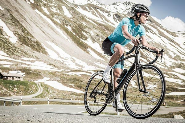 Female road cyclist in the alps