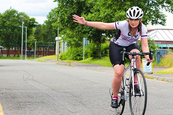 Female cyclist signalling on bike