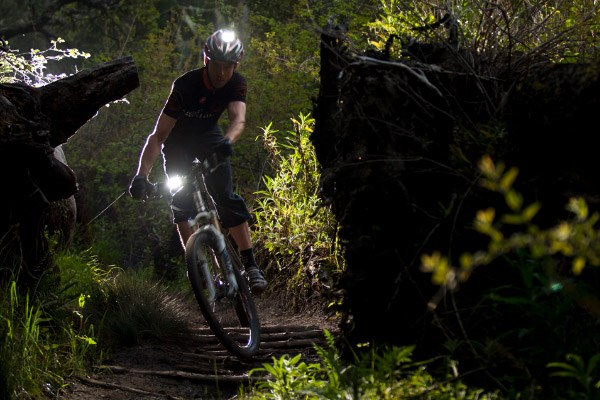 A mountain biker using lights mounted to both the handlebars and their helmet