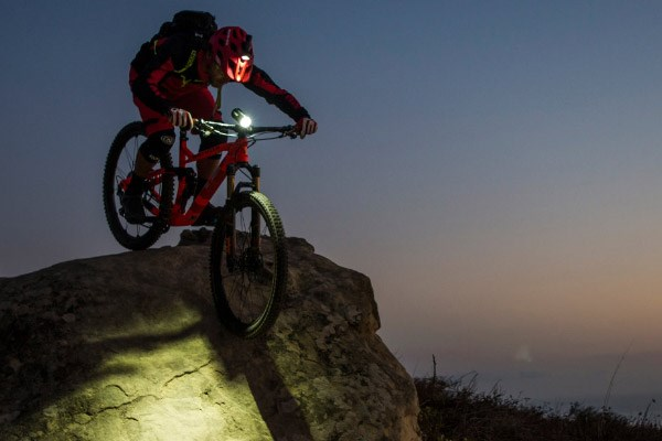 Mountain biker using advanced Exposure lights on both helmets and handle bars