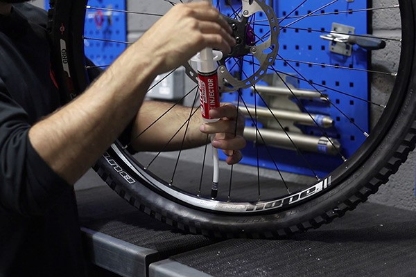 injecting sealant into a mountainbike tyre