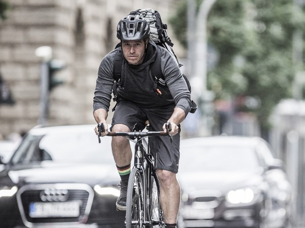 A guy in heavy urban traffic with a helmet on