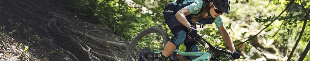 A mountain biker descending a rooty trail on a Cube Mountain Bike
