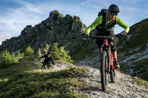 Mountain bikers at the top of a rocky, natural trail
