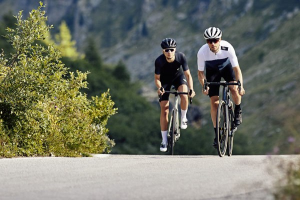 Two cyclists riding along remote mountainous roads