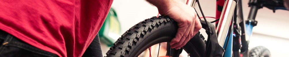 Tredz mechanic checking tyre pressure on a mountain bike