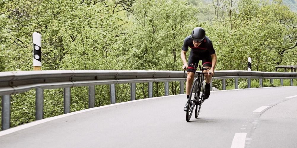 A cyclist on an empty road, riding a BMC Triathlon Bike