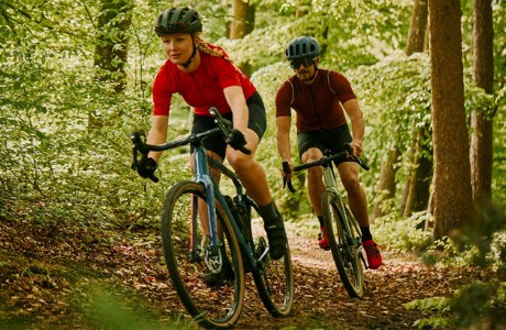 Two cyclists riding through forest trails on the BMC Unrestricted