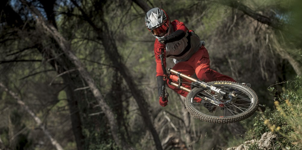 An downhill mountain biker wearing Fox Clothing and Protective Equipment