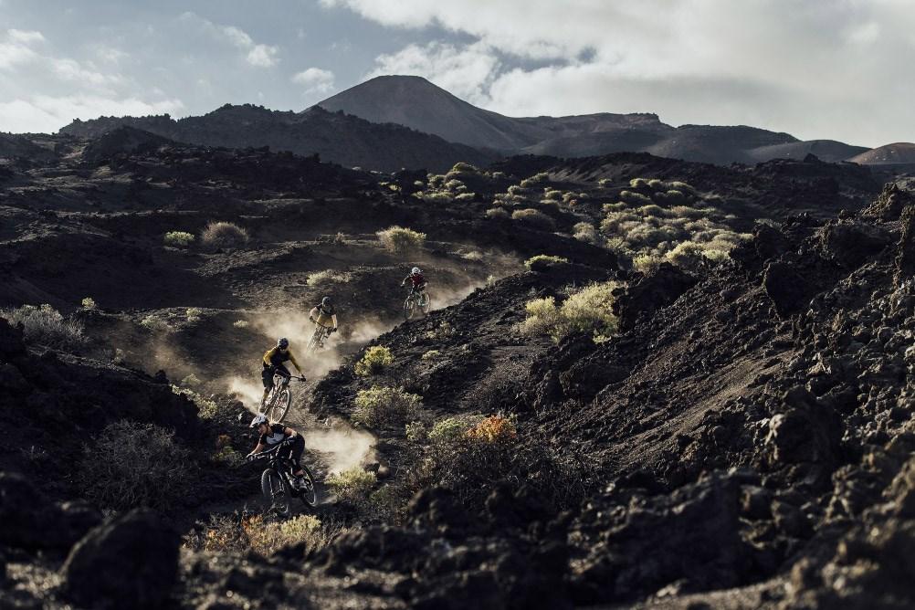 Four mountain bikers wearing ION clothing, riding through dusty terrain