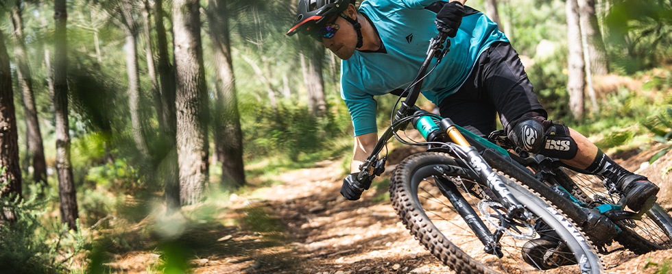 A mountain biker riding through woodland on the Merida eOne Sixty electric Mountain Bike