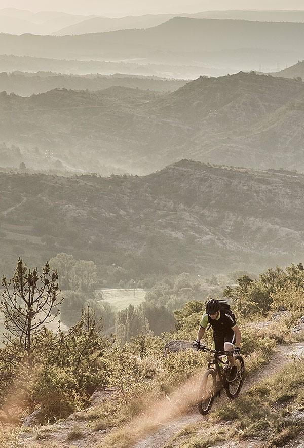 Merida mountain biker riding next to a valley