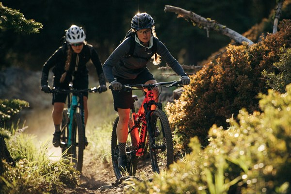 Two female mountain bikers riding through woodland