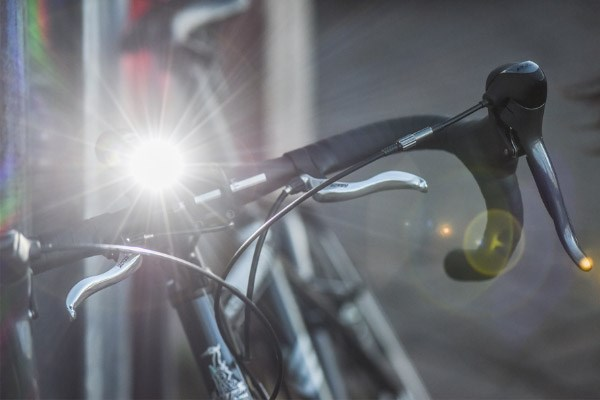A front light mounted to a road bike, shining brightly