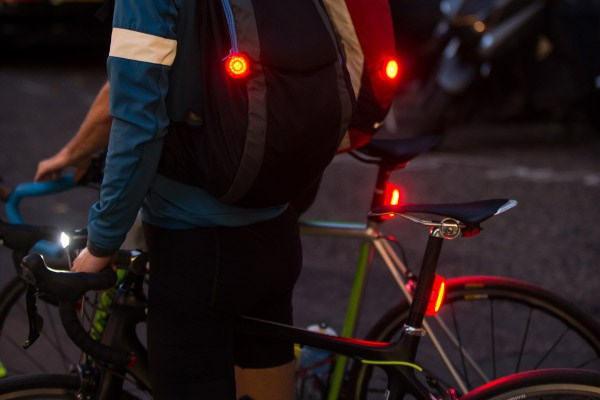 Road cyclists with rear lights mounted to backpacks and seat posts