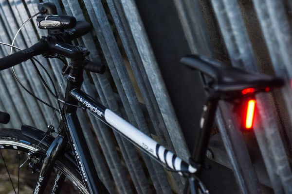 A road bike with a rear light connected to the saddle's rails