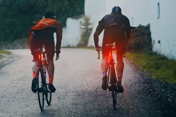 Two cyclists riding in wet conditions