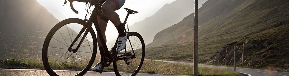Road cyclist climbing mountain silhouette