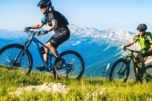 two mountain bikers riding in the mountains