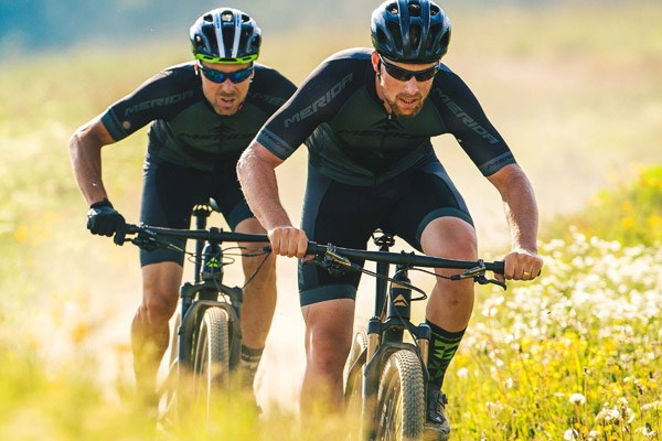Two cyclists riding lightweight, short-travel MTBs