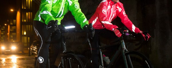 Two cyclists riding through the city with high vis jackets and bib tights with reflective panels