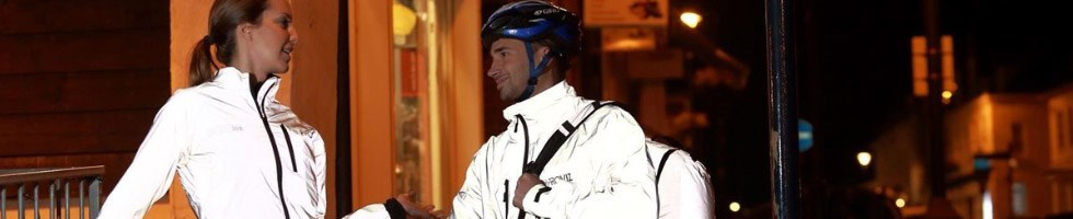 Two cyclists wearing reflective jackets at night.