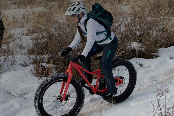 A mountain biker, riding through snow on a fat bike with breathable trousers on