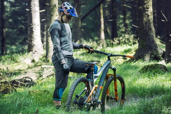 Mountain biker looking at the saddle on a Cube full-suspension MTB