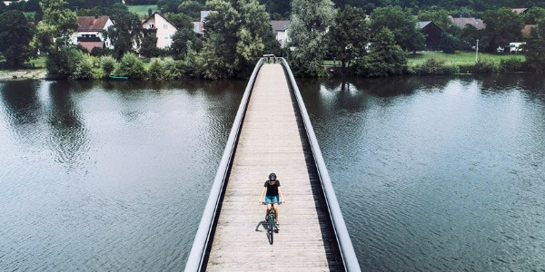 Cyclist crossing a bridge in a rural setting