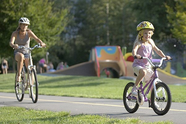 A mother and daughter cycling through a park together