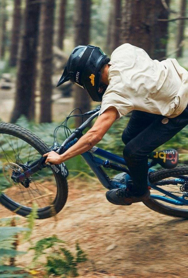 A mountain biker riding a full-suspension bike through flowing trails