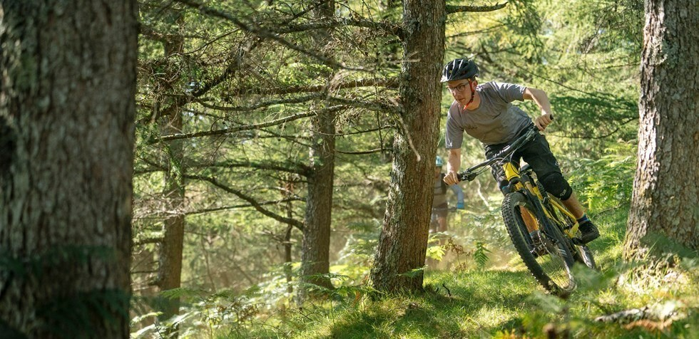 MTB rider descending through the woods on Orbea Wild FS in Spain