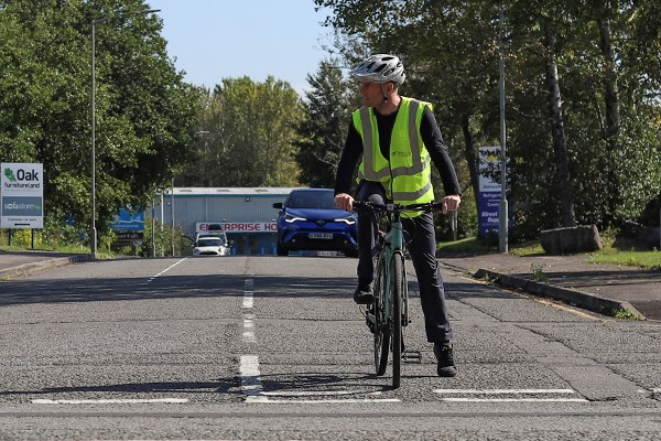 cyclist waiting to turn right onto a main road