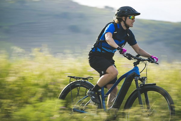 A mountain biker riding a Merida electric hardtail mountain bike through an overgrown trail