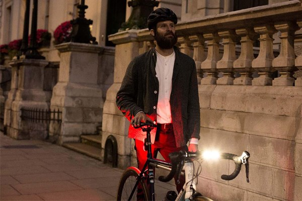 Cyclist standing by bike with lights on