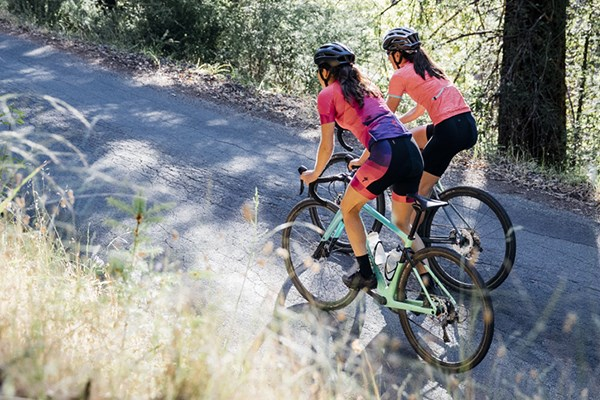 Two cyclists riding in summer cycling clothing - including bib shorts