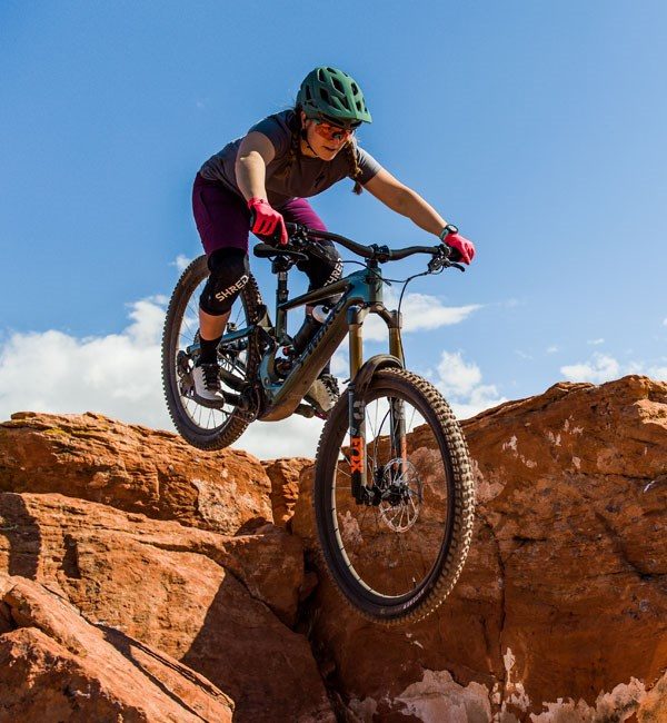 A mountain biker riding a drop-off on the new Specialized Turbo Kenevo SL