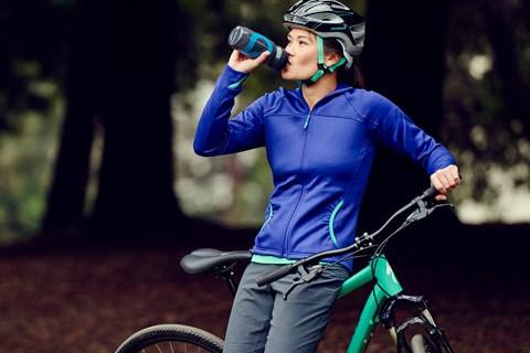 Female biker drinking water