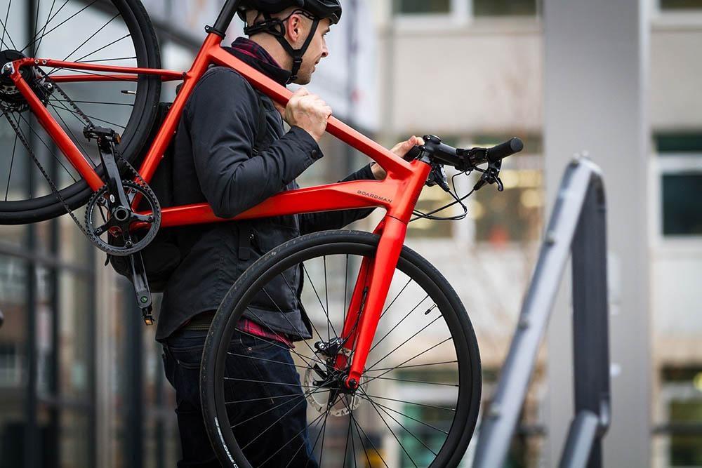 commuter with bike on shoulder