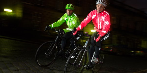 Two cyclists wear Endura jackets in bright colours with reflective detailing for good visibility, even on dark autumnal evenings