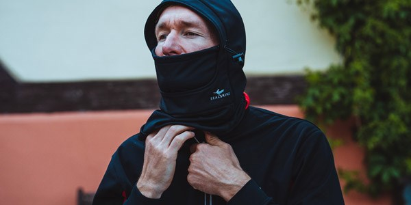 A cycle commuter wearing multiple layers, including a windproof jacket and scarf